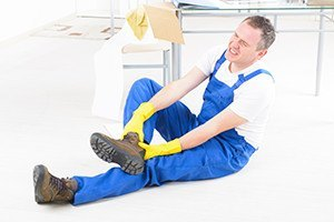 Man worker with ankle injury concept of accident at work