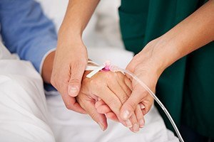 Closeup of nurse holding patients hand