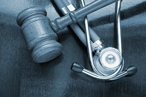 Gravel and stethoscope on wooden background