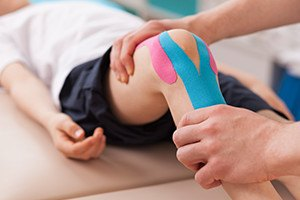 Physiotherapist doing with young excercise for knee