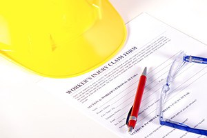 Worker injury claim hard hat with eyeglasses and pen on white background
