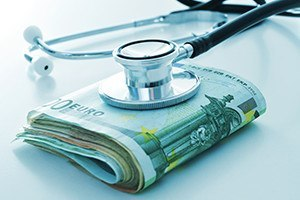 A stethoscope on a wad of euro bills depicting the concept of the health care