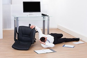 Full length of young businessman fallen from office chair